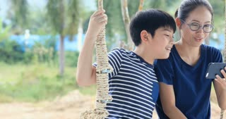 Happy asian brother and sister hand holding mobile phone on swing chair with smile face.