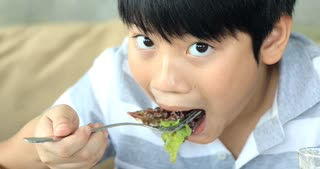 Happy asian child enjoy eating salad with yummy face. 10 01 005