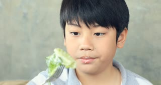 Happy asian child enjoy eating salad with yummy face.