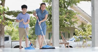 Happy asian family cleans the room. Mother and son do the cleaning in the house. A young woman and a little child boy wiped the dust and vacuumed the floor.