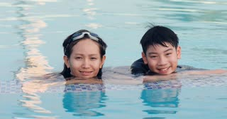 Happy asian family enjoying playing together swimming pool at water theme park