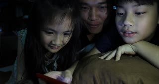 happy asian family father and child watchung on tablet computer