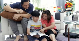 Happy asian family father mother and son reading education book together with smile at home.