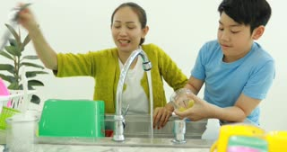 Happy asian family mother and son dish washing together at home with smile face