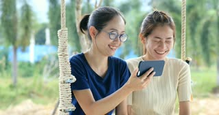 Happy asian family older sister and younger sister hand holding mobile phone on swing chair with smile face.