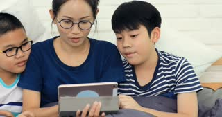 Happy asian family Sister and brother with friend playing tablet computer at home with smile face.