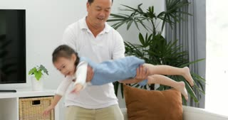 Happy Asian Father and Little Daughter having fun throws up child girl.  in the Living Room.  Father and Daughter quality time. Family time. relax time.