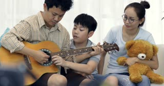 Happy asian Father playing guitar for his family at home