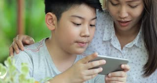Happy family mother and son playing game on mobile cell phone together.