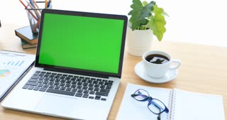 Laptop on desk with green screen.