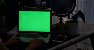 Laptop with green screen. Dark office. Dolly in . Perfect to put your own image or video.Green screen of technology being used. Chroma Key laptop