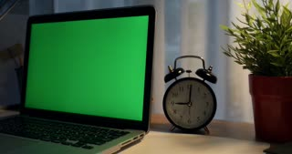 Laptop with green screen. Dark office. Dolly move right to left. Perfect to put your own image or video.Green screen of technology being used. Chroma Key laptop
