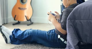 leisure, children, technology and people concept - smiling asian boy with smartphone and headphones listening to music or playing game at home
