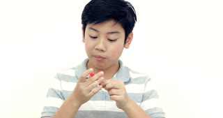 Little asian boy eating jelly and smile on white wall background