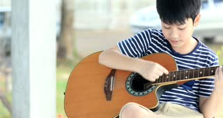 Little asian boy is playing the guitar