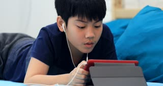 Little asian boy rest on blue bed using tablet computer with ear phone .