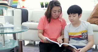 Mother and his son reading education book, mom helping his son doing your homework.