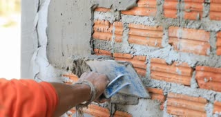 Non identify Construction workers plastering brick wall using cement at construction site