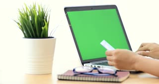 Online shopping. Young caucasian Female hand holding credit card and shopping online. With green screen on laptop computer