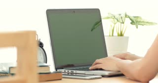 Over the shoulder shot of an Asian woman typing on a laptop computer with a key green screen .