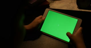 Over the shoulder view of asian boy using tablet computer with headphone, Green screen of technology being used. Chroma Key tablet.
