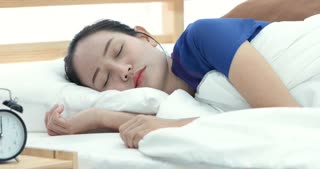 Pretty asian woman refusing to wake up lying on her bed