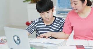 Serious Asian mother with son doing homework in the living room. Mom teaches son how to genius.