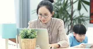 Shot of an attractive mature businesswoman working on laptop in her workstation at home with boy playing tablet computer on background.