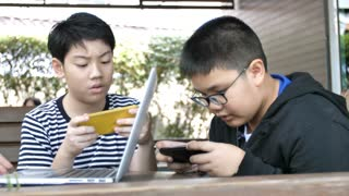 Slow motion 4K Asian mother feed cake to his son. Two boy playing mobile game on smartphone