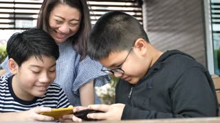 Slow motion 4K Happy asian family mother and son watching on mobile phone with smile face together.
