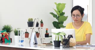 Woman in home office suffering from neck pain sitting at computer desk