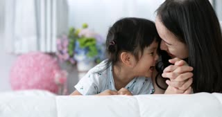 Young Asian Mother and child kissing and hugging, Resting on bed together, Motherhood Beautiful Happy Family. Young mother playing with her baby.