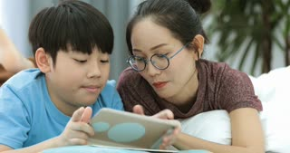 Young asian mother with son watching and playing tablet computer together at home.