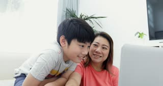 Young Asian mother working  on the laptop computer with his son with smile face .