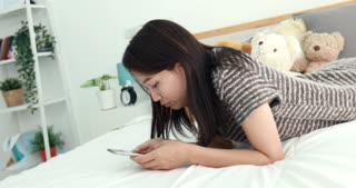 Young asian woman using smart phone on the bed