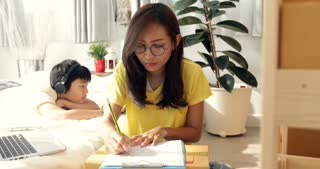 Young asian woman with child boy working and packing Thailand post box to send  ,Young business start up.  SME, Delivery Project,