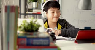 Young teenage student listen to music from tablet computer and doing homework at home, Dolly move left to right.