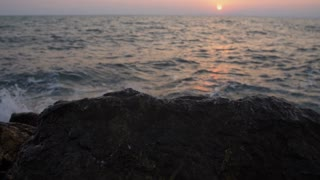 Water splashing against rocks with sunset (super slow motion)