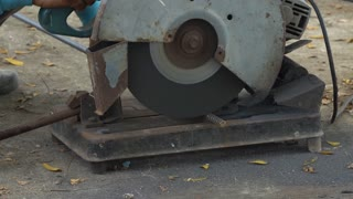 Worker Sawing cut Metal Line With a Circular Saw Sparks on Location building .