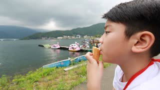 Young Asian boy eating ice cream.with lake side view, smile face.
