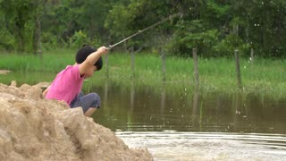 Young asian boy playing in mud puddle near the river