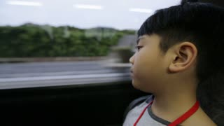 Young asian boy riding bus and looking out the window