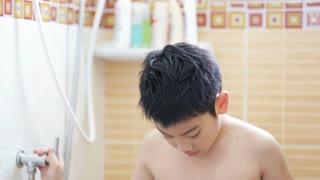 Young Asian boy washing his hair in bathroom