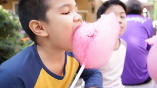 Young asian boys sitting near attractions. they eat sweets and look very cheerful and happy