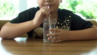Young Asian child drinking a glass of water .