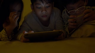 Young asian child playing game on mobile phone, The light from the game reflect on their face .