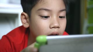 Young Asian child using a digital tablet together .