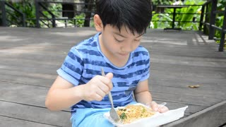 young asian cute boy eating fried chiness noodles.,in foam box