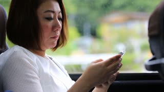 Young asian woman using smartphone while riding bus