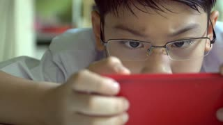 Young happy asian boy playing game with cellphone .